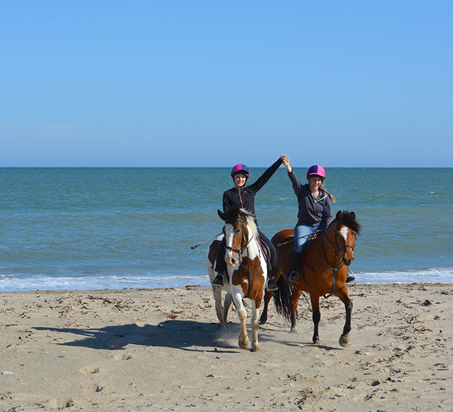 happy girls on horses on the beach